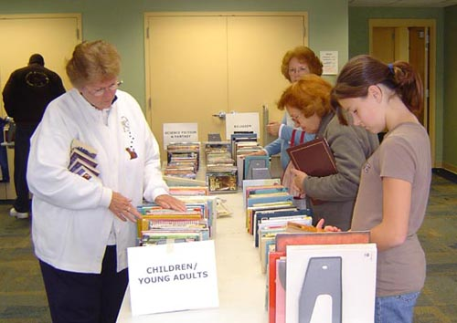 Library patrons browsing the selection at a book sale